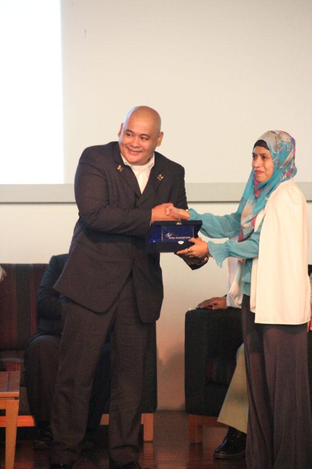 Ibu Nurul Sukma Lestari menyerahkan plakat kepada Bapak Teguh Perwira perwakilan seluruh nara sumber
